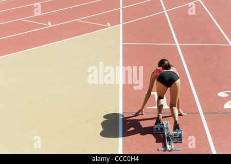 Woman crouched in starting position on running track, rear view - Stock Photo