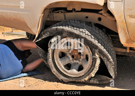 Driver fixing blowout tire of four-wheel drive vehicle in the Namib desert, Namibia - Stock Photo