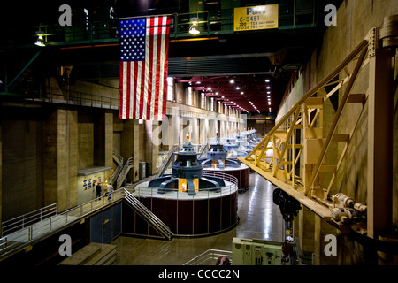 An American flag decorates one of the hydroelectric power plants at Hoover Dam on the Colorado River. Note workmen. - Stock Photo