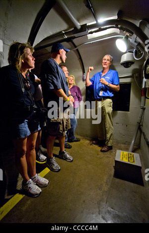 A uniformed guide explains an earthquake detector (lower right) to a tour group in an inspection tunnel at Hoover - Stock Photo