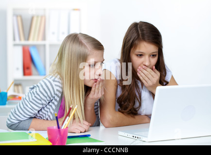 Two astounded girls looking at laptop screen in college - Stock Photo