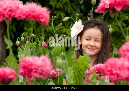 Sweet little girl on the field with pink poppies - Stock Photo