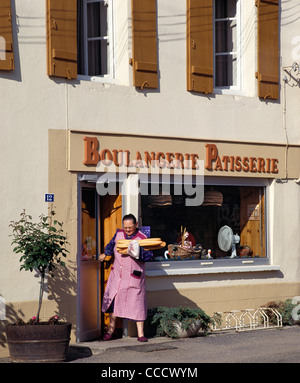Woman coming out of Boulangerie with baguettes. Puligny-Montrachet, Côte d'Or, France. - Stock Photo