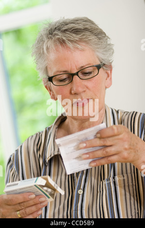 Older female person is reading an instruction leaflet - Stock Photo
