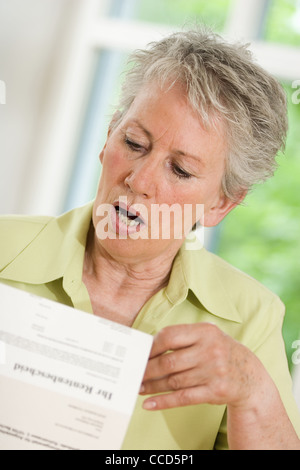 Older female person looking at pension award - Stock Photo