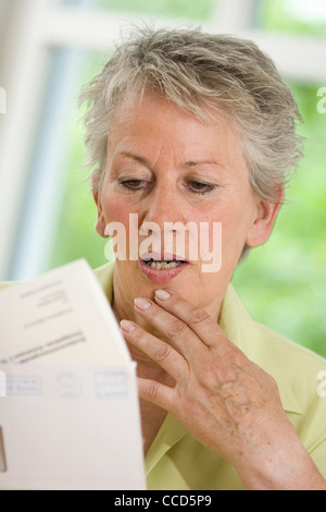 Older female person looking at official letter - Stock Photo