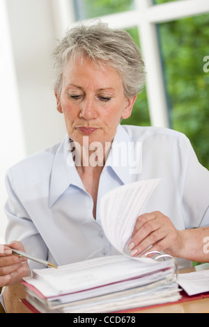 Older female person checking records - Stock Photo