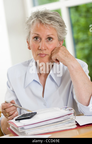 Older female person with a calculator - Stock Photo