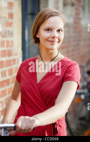 Young blond woman in red dress standing on a street with old bicycle - Stock Photo