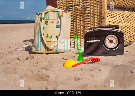 a beach chair, alongside are a radio, a beach bag and beach toys