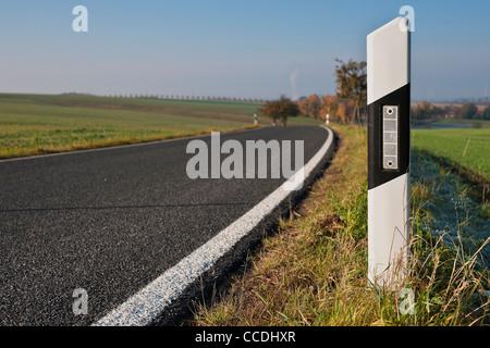 Detailansicht eines Leitpfosten rechts auf einer Landstraße   Detail photo of one reflector post on the right on - Stock Photo