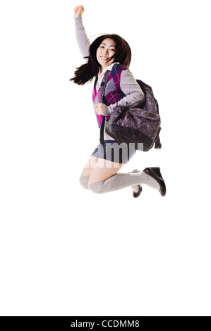 Female Chinese student with a backpack on a white background jumping into the air. - Stock Photo
