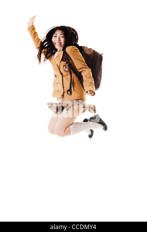 Female Chinese student wearing a backpack on a white background jumping into the air. - Stock Photo