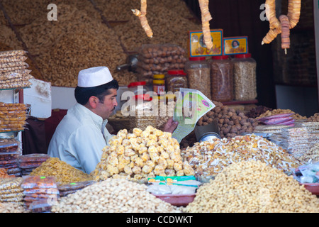 Vendor reading a newspaper at a snack shop, Murree, Punjab Province, Pakistan - Stock Photo