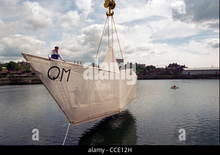 Sculptor George Wyllie's (on bow) Paper boat is craned into the water at the Consafe Shipyard in Burntisland, Fife - Stock Photo
