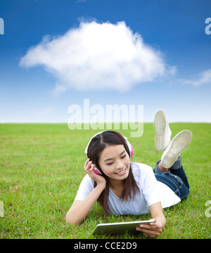 happy girl using touch pad computer with headphone on the meadow - Stock Photo