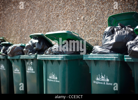 Overflowing Domestic Wheelie Bins against a wall in Brighton and Hove, UK - Stock Photo