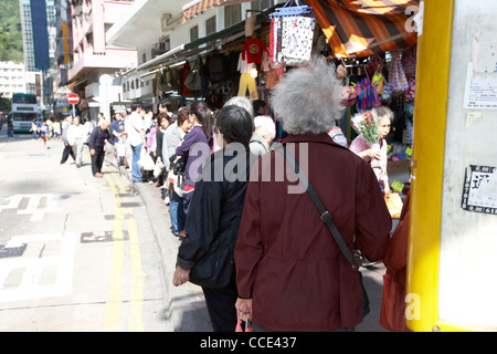 people including elderly woman waiting for a bus at a bus stop aberdeen hong kong hksar china asia - Stock Photo