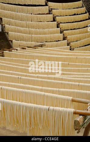 Racks of raw noodles hanging outside to dry in Fuli near Yangshuo China - Stock Photo
