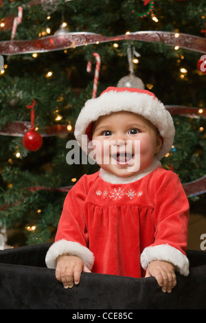 Happy baby girl in front of Christmas Tree, - Stock Photo