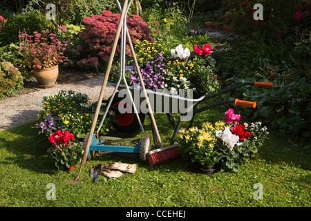 Wheelbarrow, grass mower, garden equipment, tools, preparing for planting new plants in the garden on early September - Stock Photo