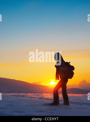 Woman traveler hiking in winter mountains, trekking in wintertime cold snowy weather, girl silhouette over natural - Stock Photo