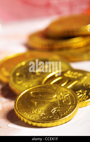Heap of ten euro cent coins close up on banknote - Stock Photo