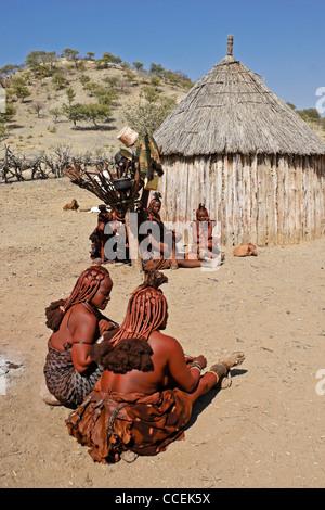 Himba women in village near Opuwo, Namibia - Stock Photo