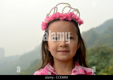 A beautiful young girl wearing a princess crown looks into the camera. - Stock Photo