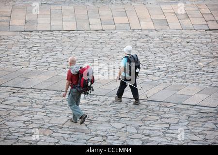 Two pligrims arriving at the Cathedral of Santiago de Compostela in the Praza da Obradoiro - Stock Photo