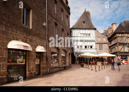 Street scene in Dinan, Brittany France. Two young women walk through the town centre, with its old half timbered - Stock Photo