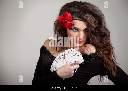 Beautiful gypsy with curly hair and cards in their hands - Stock Photo