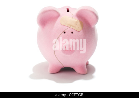 A broken piggy bank with a sticking plaster - Stock Photo