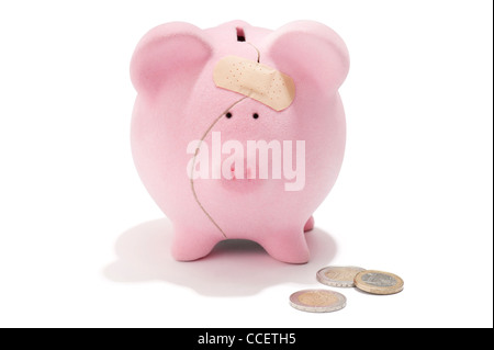 A broken piggy bank with sticking plaster and Euro coins - Stock Photo