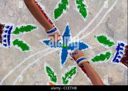 India sisters making a Rangoli design at Sankranthi festival. Puttaparthi, Andhra Pradesh, India - Stock Photo
