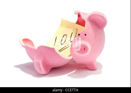 An I.O.U note inside a broken piggy bank - Stock Photo