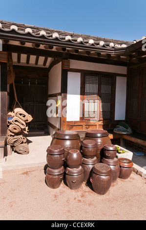Hanok (Korean traditional house with timber frames and clay tiles) and its courtyard.  Clay pots are on display. - Stock Photo