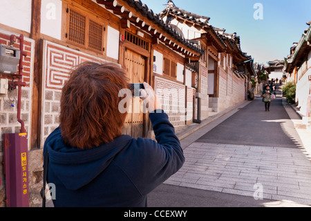 a tourist taking a photograph of traditional timber frame houses with his mobile phone in Bukchon Hanok Village, - Stock Photo