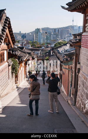 Tourists in Bukchon Hanok Village where there are old traditional Korean houses.  You can see modern buildings in - Stock Photo