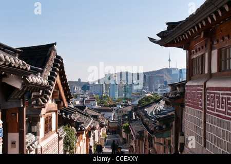 Juxtaposition of architecture.  Old traditional Korean houses in Bukchon Hanok Village and modern buildings in the - Stock Photo