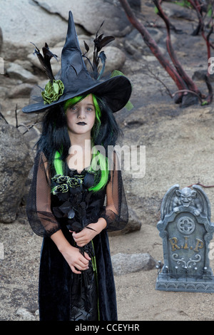 Portrait of young girl costumed as a witch - Stock Photo