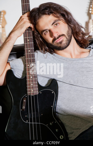 Portrait of young man holding guitar - Stock Photo