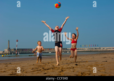 Children playing with a ball on Margate beach. Isle of Thanet. Kent England - Stock Photo
