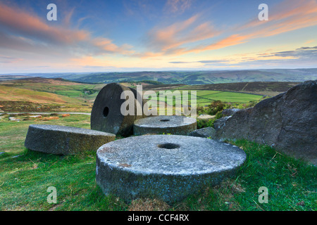 Millstones on Stanage Edge in the Peak District National Park.  Captured at sunset with the Hope Valley in the distance - Stock Photo