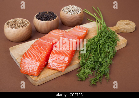 Still life with two slices trout fillet and spices on brown background - Stock Photo
