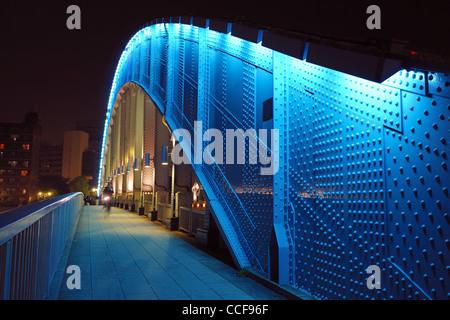 pedestrian way along the metallic arc structure of Eitai bridge in Tokyo - Stock Photo