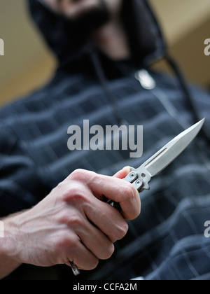 Knife Crime. Hooded Male Brandishing a Butterfly Knife. - Stock Photo