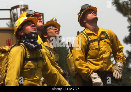 Jul 16, 2004; Carson City, CA, USA; Bureau of Indian Affairs firefighters watch a team of aircraft conduct an aerial assault on the Waterfall Fire Friday, July 16, 2004 in the Lakeview Estates area of Carson City, Nevada. From left are ADAM FIMBY, CHRIS LOVETT, MALLORY BOZEMAN and CORY BREWER. Hilly Stock Photo