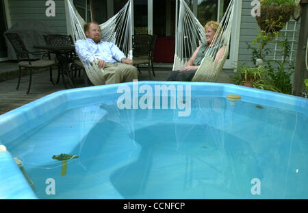 Stuart (cq) and Claudia Wentworth sit next to their hot tub, which is kept warm using one of their solar panels, - Stock Photo