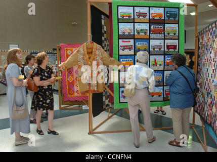 People browse at the annual quilt show at Charlotte Wood Middle School as a quilt titled 'What A Long Wild Trip - Stock Photo